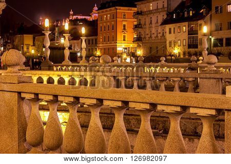 Triple bridge in Ljubljana  with many lights around at night