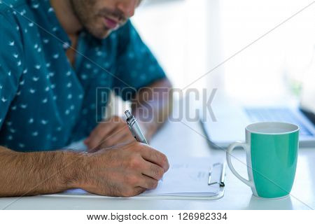 Mid-section of man writing on clipboard with coffee mug on table at home