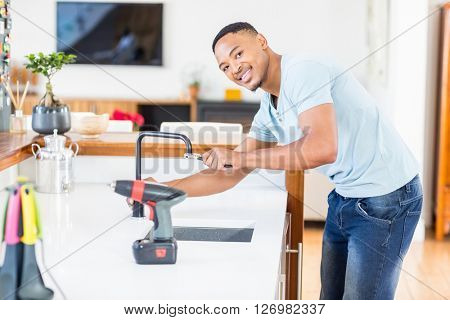 Portrait of man tightening tap with a wrench in kitchen