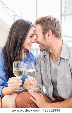 Young couple toasting wine glasses at home