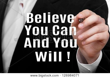 Man writing Believe You Can And You Will on transparent wipe board.
