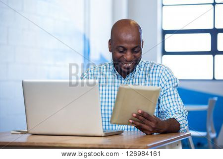 Man using digital tablet with laptop on table in office