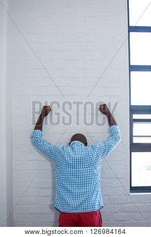 Rear view of upset man leaning against wall in office