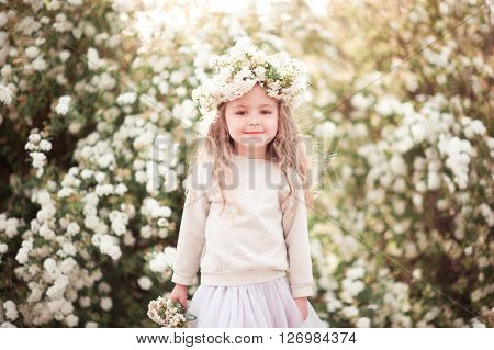 Smiling kid girl 3-4 year old wearing flower wreath outdoors. Looking at camera.