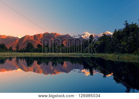 Twin Peaks Reflect In The Beautiful Lake Matheson At Sunset, New Zealand