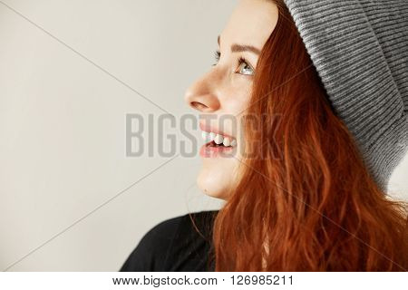 Side View Of Attractive Happy Young Freckled Female With Long Loose Coppery Hair In Gray Cap Looking