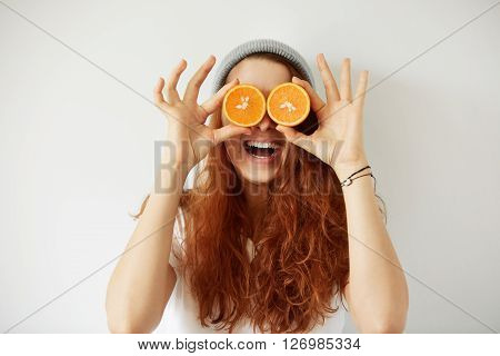Close Up Studio Portrait Of Young Smiling Female Holding Halves Of Oranges At Her Eyes. Headshot Of