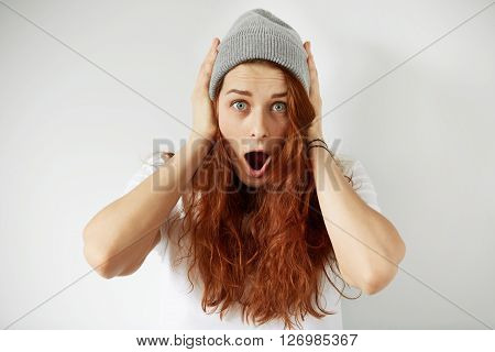 Headshot Of Cute Redhead Girl In White T-shirt And Gray Cap Looking With Surprise At The Camera. Clo