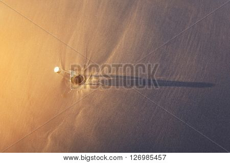 Top view, bottle on sand with shade and shadow, vintage tone