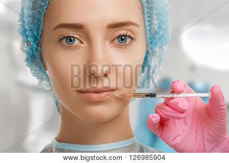 Close Up Shot Of Doctor's Hand In Rubber Sterile Glove Holding Injection Syringe, Giving Woman Patie