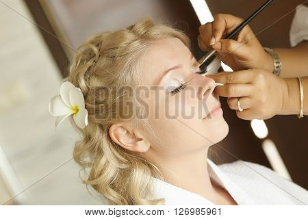 Beautiful cute blond bride doing makeup before wedding day. Long lashes white flowers in hair smilling and happy. Perfect wedding preparation.