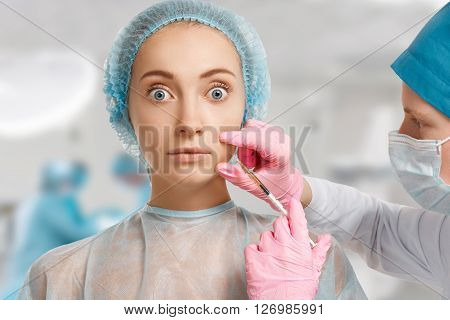 Portrait Of Scared And Shocked Young Caucasian Woman Getting Cosmetic Injection In Face With Medical