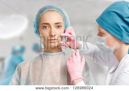 Close up view of beautiful female getting facial injection in her cheek against clinic interior background. Young Caucasian woman having cosmetic procedure in beauty clinic. Aesthetic medicine
