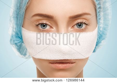 Close-up Isolated View Of Bandaged Face After Cosmetic Operation. Headshot Of Young Caucasian Woman