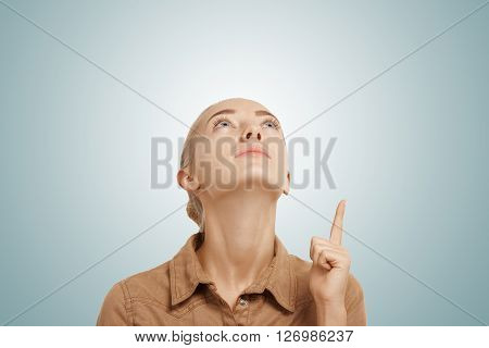 Close Up View Of Young Beautiful Caucasian Blonde Woman Pointing And Looking Up At Copy Space For Yo