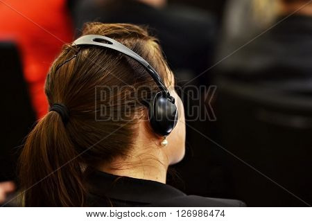 Unrecognizable woman using headphones for translation during event