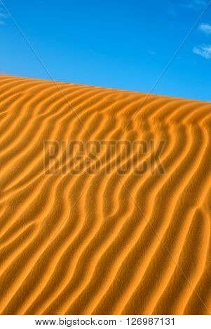 Detail of ripples in orange sand dune on a clear day