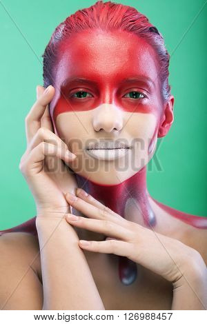 young woman with creative face-art over green background