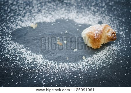 Concept of the bittersweet feeling of finishing a delicious croissant. Outlined with powdered sugar. Selective focus.