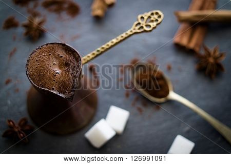 Black turkish coffee with sugar cubes cinnamon sticks and anise star on dark stone slate. Selective focus on coffee foam.