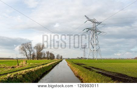 Power lines and pylons in a rural area in the Netherlands. It's a sunny day with a cloudy sky in the winter season