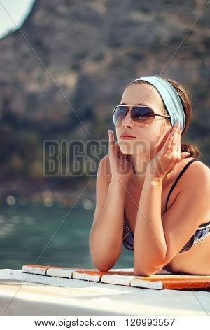girl sunbathes on sunbed. Woman on vacation. Woman lying on background of sea and mountains