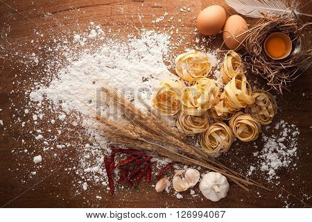 fettuccine pasta italian food still life rustic flat lay wood background tagliatelle alfredo garlic chili pepper yolk eggs
