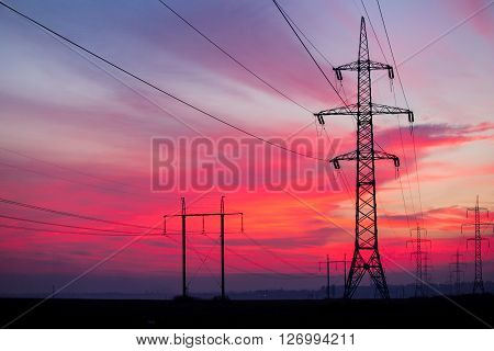 High voltage electricity pylon system on sunrise background.