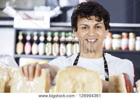 Confident Salesman Arranging Cheese In Shop