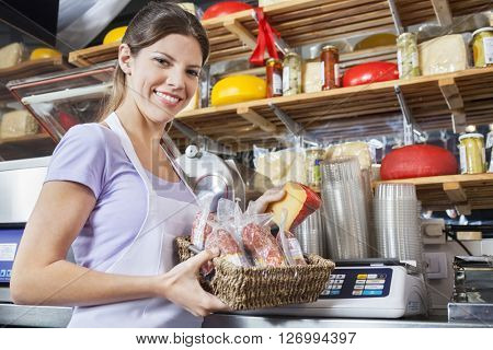 Confident Saleswoman Weighing Cheese At Grocery Store
