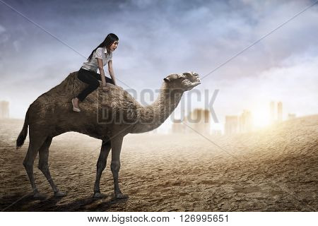 Image Of Asian Business Woman Riding Camel