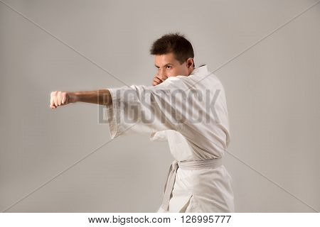 Young man in white kimono and white belt training martial art over gray background