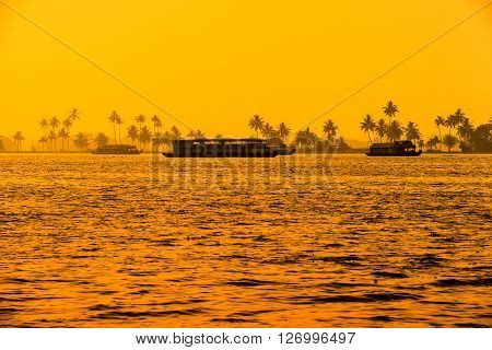 beautiful sunset landscape with houseboats at backwaters Kerala and silhouette of palm trees travel background India