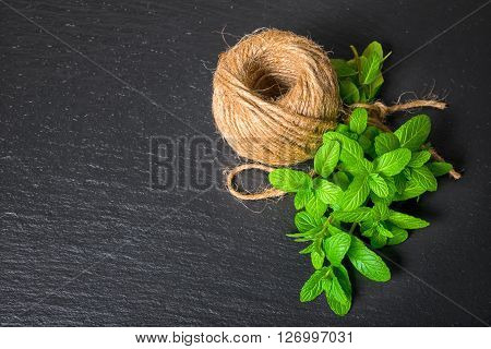 Top View Of Beautiful Bunch Fresh Green Melissa Officinalis Tied Twine And Yarn On Slate Background,