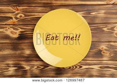 Yellow plate on a brown wooden table, eat me