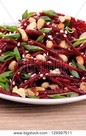 Salad of fresh grated beets onions flavored with nuts and sesame seeds