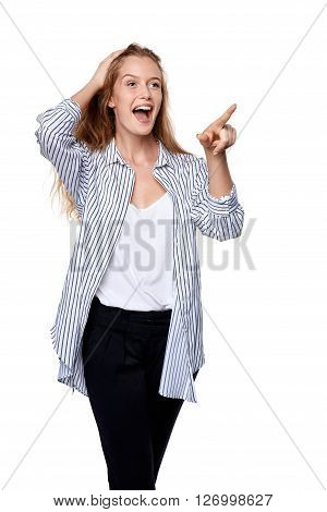 Happy excited woman pointing to the side at blank copy space, over white background
