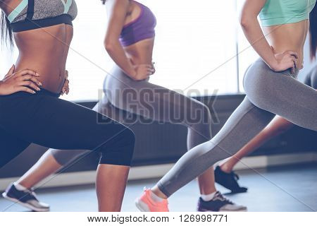 Exercising for perfect shape. Side view part of young women with perfect buttocks in sportswear exercising while standing in front of window at gym