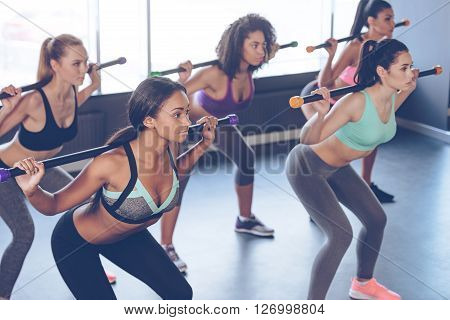 Concentrated at their workout. Beautiful young women with perfect bodies in sportswear exercising with barre while standing in front of window at gym