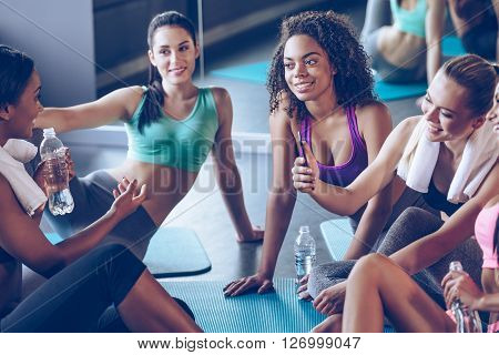 They deserve a little rest. Beautiful young women in sportswear discussing something with smile and using smartphone while sitting on exercise mat at gym