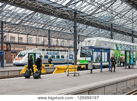 HELSINKI, FINLAND - APRIL 23, 2016: The Central Railway Station. People walk along the platform near the double decker trains and Allegro Train