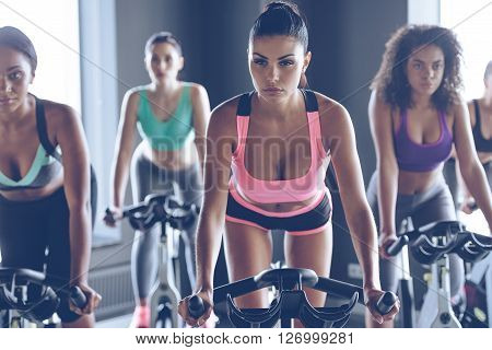Up to speed with their fitness goals. Young beautiful women with perfect bodies in sportswear looking at camera while cycling at gym