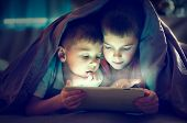 Two kids using tablet pc under blanket at night. Brothers with tablet computer in a dark room poster