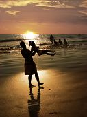 pic of beach sunset  - father playing with his daughter on the beach at sunset - JPG
