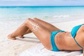 Sunscreen sun drawing lotion on suntan legs relaxing tanning on tropical beach holiday. Sexy bikini  poster