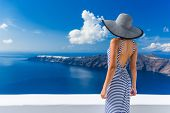 Luxury travel vacation woman looking at view on Santorini famous Europe travel destination. Elegant  poster