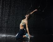 picture of dancing rain  - The beautiful girl dancing in water under rain on a black background - JPG