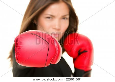 Boxing business woman punching towards camera wearing boxing gloves. Focus on boxing glove. Businesswoman isolated on white background.