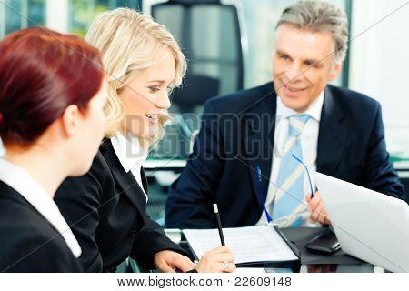 Negócios - reunião em um escritório; os empresários estão discutindo um documento