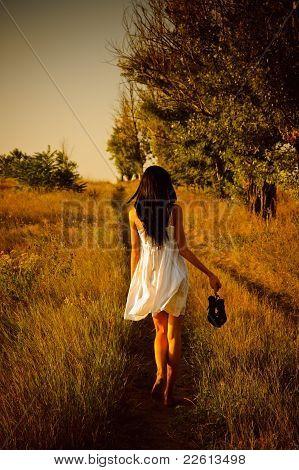 Menina com os pés descalços em vestido branco com os sapatos na mão é no campo. Vista traseira